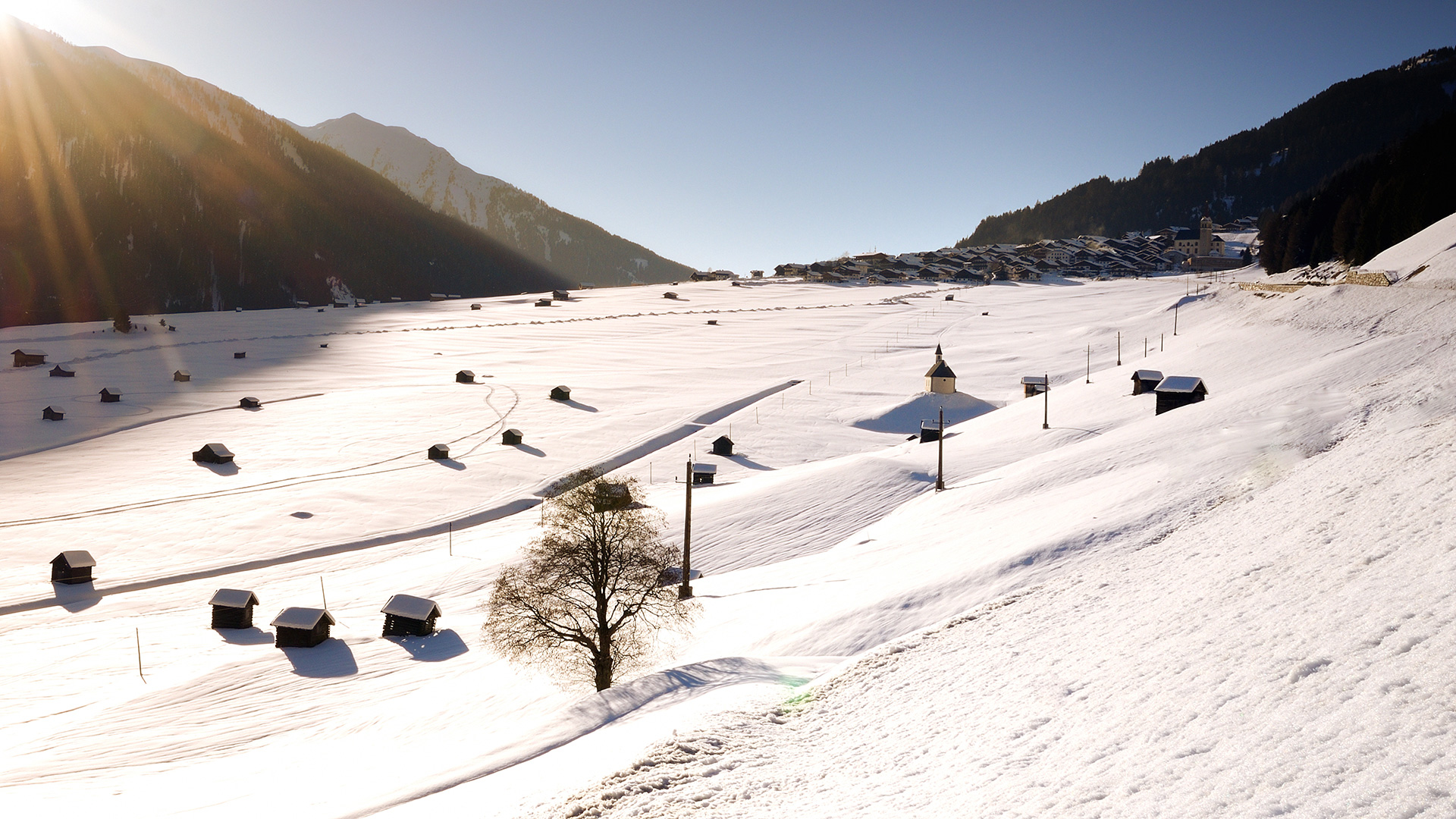 Winter landscape with barns in the mountains