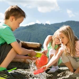 Kinder spielen mit Wasser am Berg