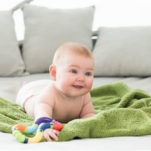 Baby liegt auf einer Decke auf einem Sofa