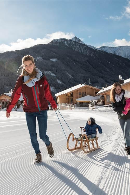 Frauen mit Kindern ziehen einen Schlitten im Schnee