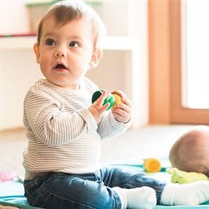 Babys befinden sich auf einer Decke mit Spielsachen
