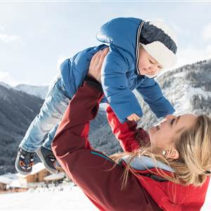 Woman lifts her child up in winter landscape