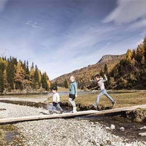 Kinder gehen auf einer schmalen Holzbrücke über einen Bach