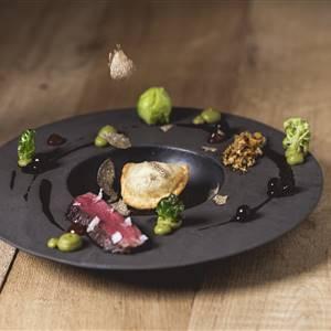 Verschiedenes Essen liegt auf einem schwarzem Teller