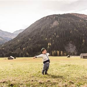 Kind in Tracht auf einer Wiese im Sommer