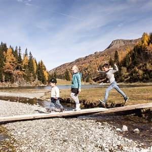 Children walking on a wooden board on the riverbed