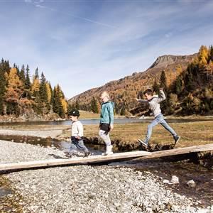 Kinder laufen über ein Holzbrett am Flussbett