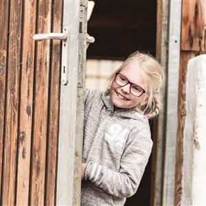 Girl looking through a door gap