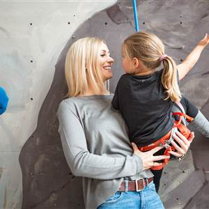Mother with daughter at a climbing wall