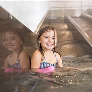 Kind auf einer Wasserrutsche in einem Hotelbereich