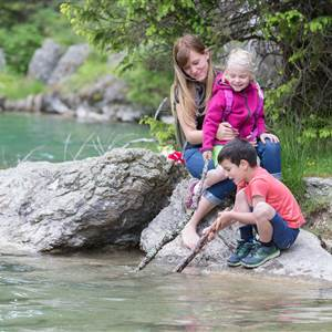 Mother sits with two children at a river