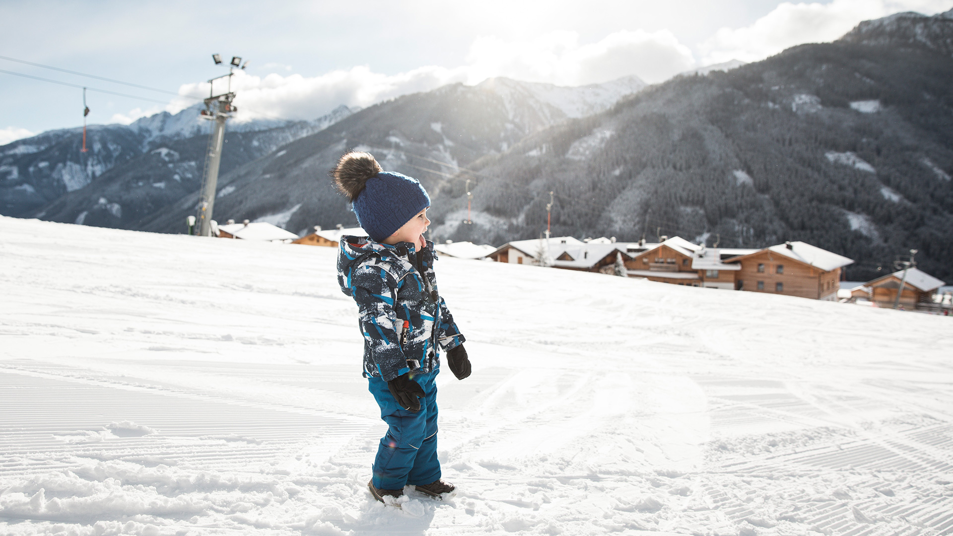 Small child in ski suit standing on ski slope