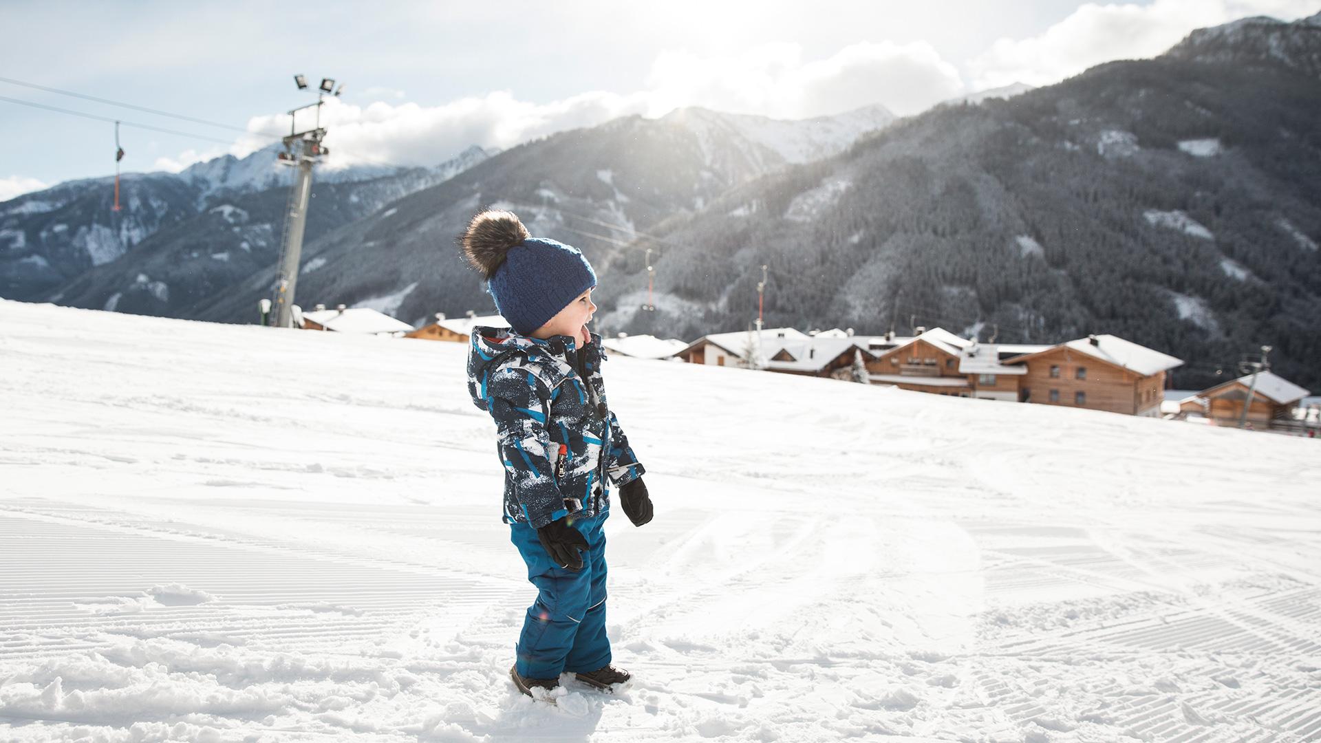 Kleines Kind im Schianzug steht auf Skipiste